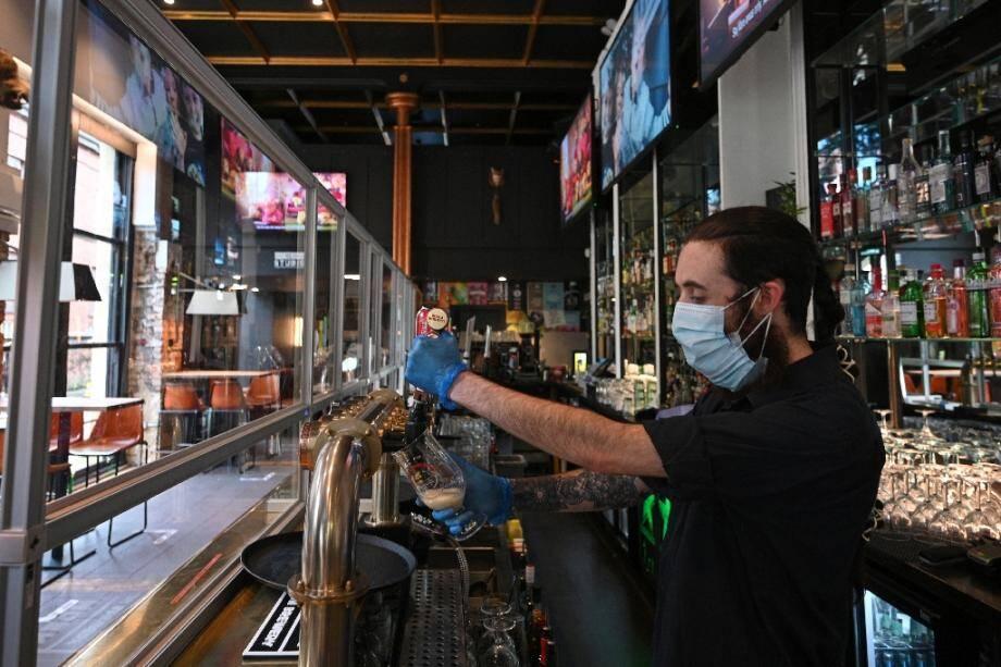 Un barmaid remplit un verre de bière dans un bar à Manchester, le 4 juilet 2020