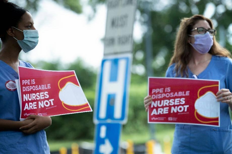 Yuhana Gidey (L), une infirmière qui a survécu au coronavirus, manifeste pour demander de meilleurs équipements de protection devant le centre hospitalier MedStar de Washington le 23 juillet 2020