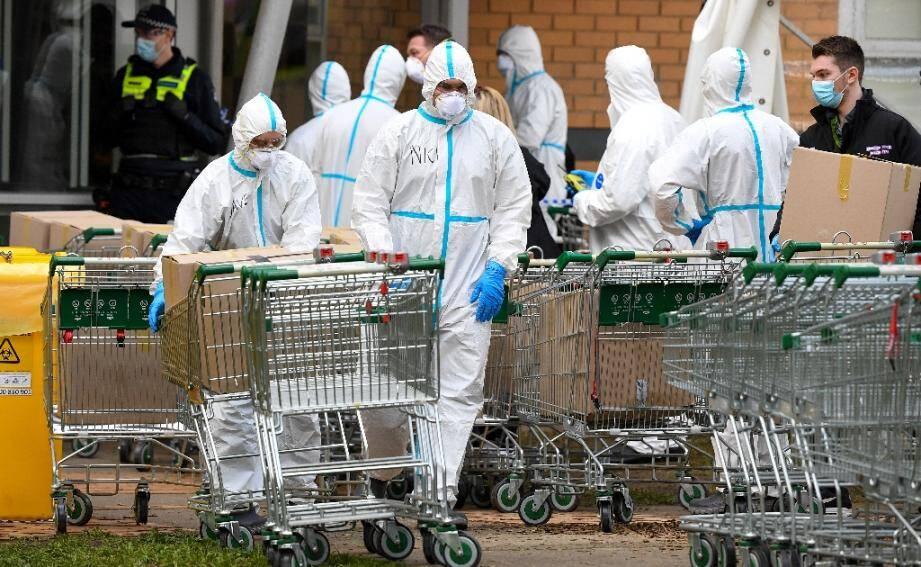 Des membres du département des pompiers préparent des colis à distribuer aux habitants à Melbourne, le 9 juillet 2020 alors que la ville est reconfinée