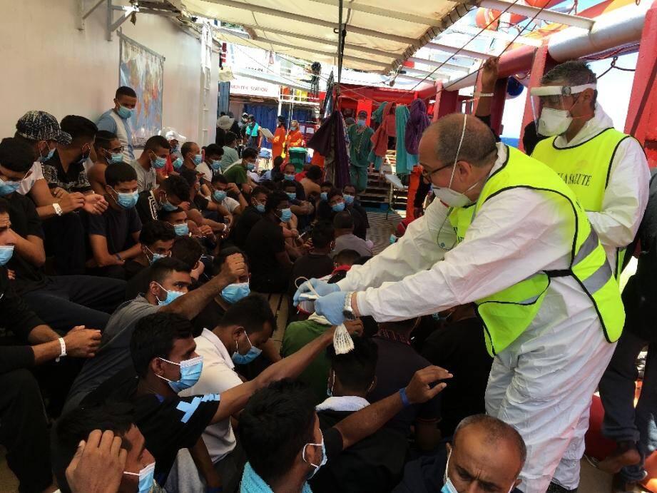 Un médecin italien distribue des bracelets numérotés à des migrans secourus sur le navire humanitaire Ocean Viking, le 5 juillet 2020 en Méditerranée