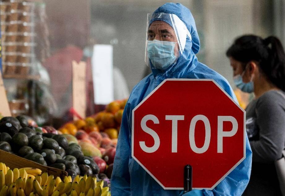 Un employé revêtu d'une combinaison de protection devant un marché régule le flux des clients, le 18 mai 2020