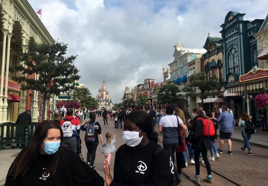 Des visiteurs portant un masque se promènent dans la rue principale de Disneyland Paris, le jour de la réouverture le 15 juillet 2020