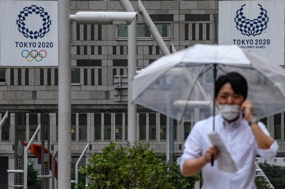 Un homme marche près du siège du gouvernement métropolitain de Tokyo où l'on aperçoit des affiches des JO-2020. Photo prise le 13 juillet 2020.