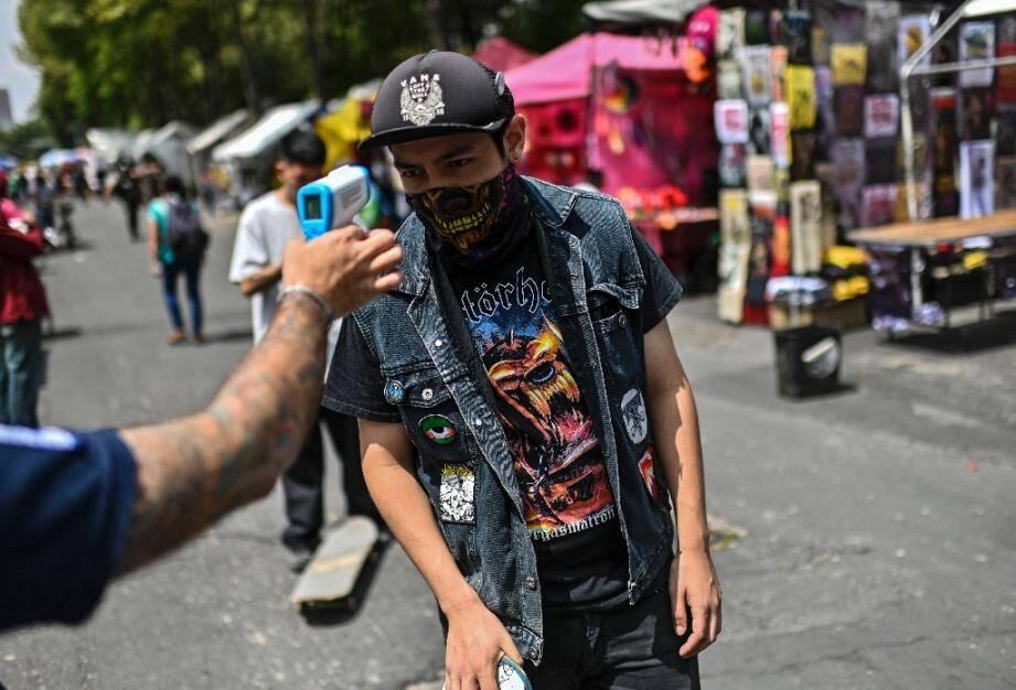 Un jeune homme se voit contrôler sa température à l'entrée du marché aux  puces d'El Chopo à Mexico City, le 25 juillet 2020