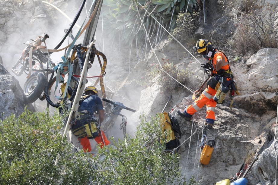 Armés d'un perforateur, les cordistes effectuent des forages en périphérie du bloc rocheux instable afin de le «confiner» grâce à un filet de protection.Photo Cyril Dodergny