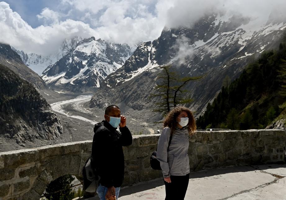 Des touristes posent devant la Mer de Glace, un glacier situé dans le massif du Mont-Balc, dans la Haute-Savoie.