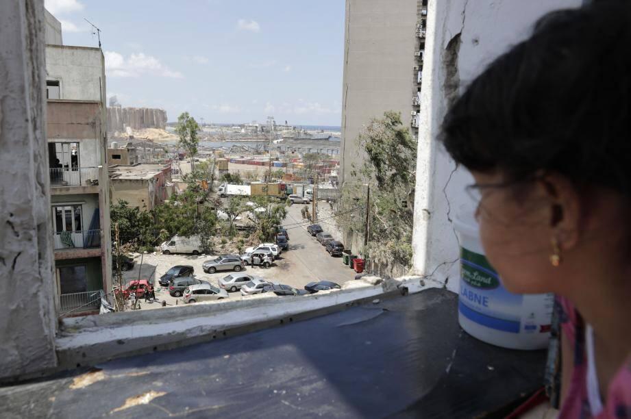 Une petite fille regarde la destruction du port de Beyrouth depuis sa fenêtre.