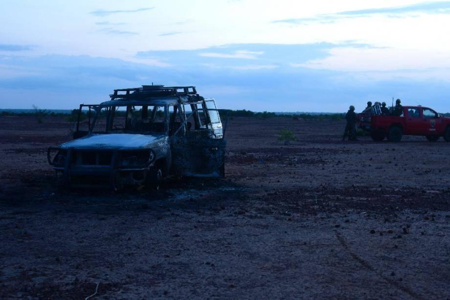 Des gendarmes nigériens près du véhicule calciné dans lequel huit personnes ont été tuées, le 9 août 2020 dans la zone de Kouré, au sud-ouest du Niger.