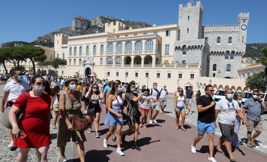 Les touristes, tous masqués, après la relève de la garde sur la place du Palais princier.
