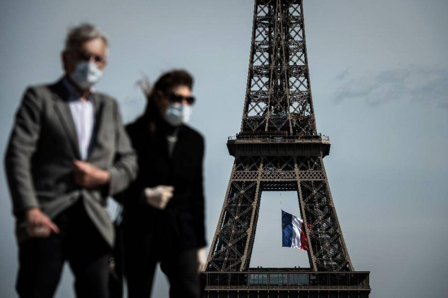 Un homme et une femme portant un masque devant la Tour Eiffel à Paris le 11 mai 2020