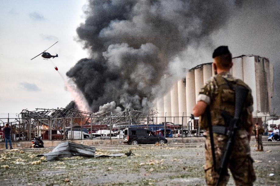 Des soldats libanais devant un hélicoptère tentant d'éteindre l'incendie provoqué par deux explosions sur le port de Beyrouth, au Liban le 4 août 2020