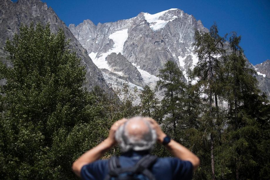 Un homme observe avec des jumelles le glacier de Planpincieux à Courmayeur, le 6 août 2020 au Val Ferret, en Italie