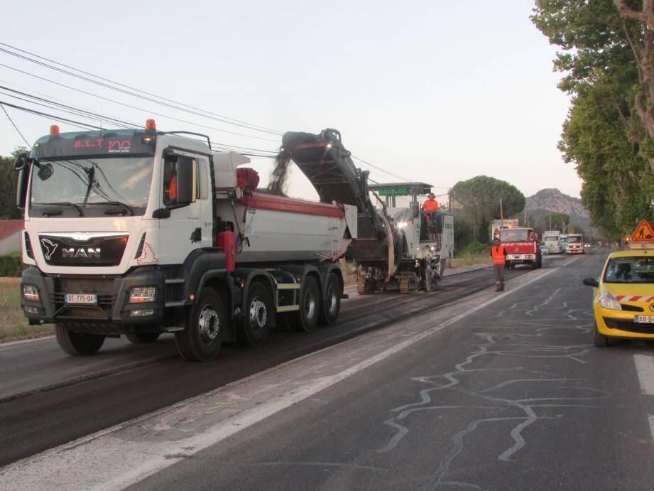 Précédée du camion dans lequel se déverse le bitume enlevé, la raboteuse entre en action. Les coups de klaxon qu'entendent les riverains signifient au conducteur du camion qu'il peut avancer.