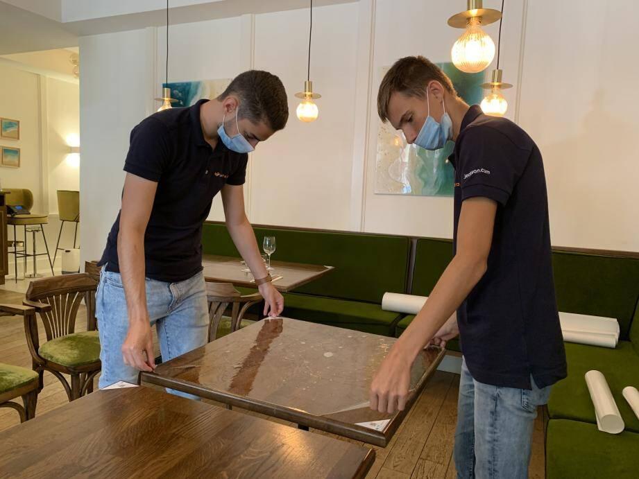 Les employés couvrent une table d'un film de protection invisible et antimicrobien. Une découpe et personnalisation, rare en France, réalisée à Puget-sur-Argens.