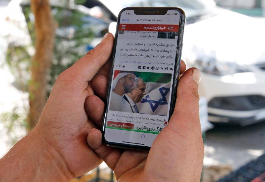 Un homme consulte sur son smartphone le site web de l'agence Tasnim News sur l'accord historique de normalisation des relations entre les Emirats arabes unis et Israël, le 14 aout 2020 à Téhéran, en Iran