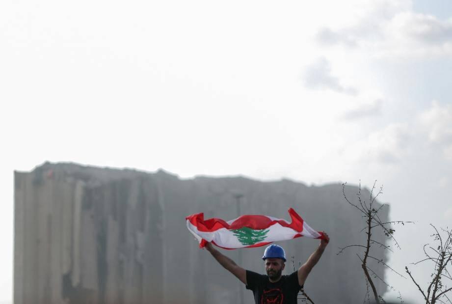 Un homme brandit un drapeau libanais lors d'une cérémonie en hommage aux victimes de l'explosion au port de Beyrouth, le 11 août 2020.