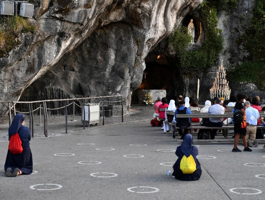Des pélerins prient devant la Grotte du sanctuaire de Lourdes, le 14 août 2020  dans les Hautes-Pyrénées