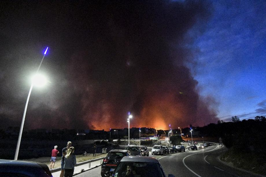 Des personnes regardent les panaches de fumée d'un incendie à Sausset-les-Pins, près de Marseille, le 4 août 2020