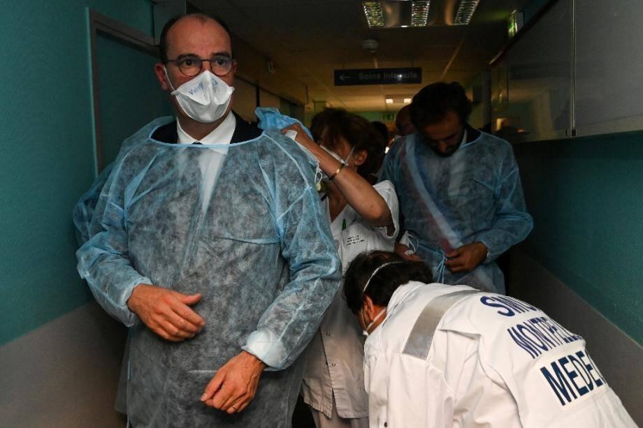 Jean Castex, assisté par des soignants pour mettre une combinaison, le 11 août 2020 lors d'un déplacement au CHU de Montpellier