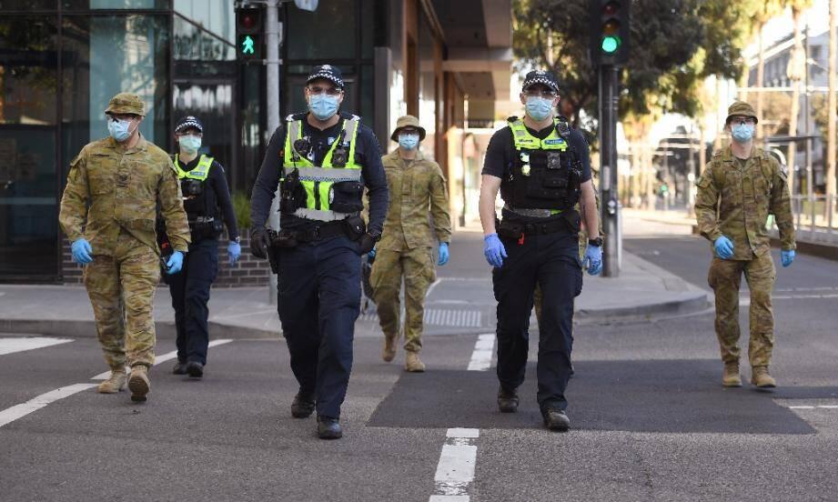 Des policiers et des soldats en patrouille à Melbourne (Australie) le 2 août 2020 après l'instauration d'un couvre-feu en raison du coronavirus