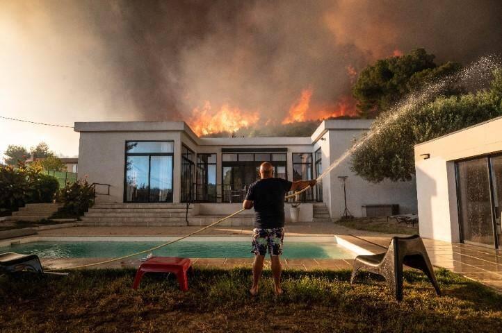 Un homme tente de maitriser le feu avant d'être évacué de sa maison à La Couronne, près de Marseille le 4 août 2020 où un violent incendie ravage l'ouest de la ville.