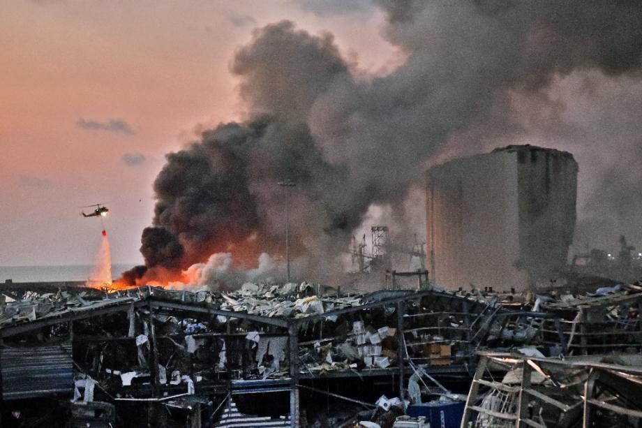 Un hélicopère tente d'éteindre le feu déclaré suite aux explosions sur le port de Beyrouth le 4 août 2020