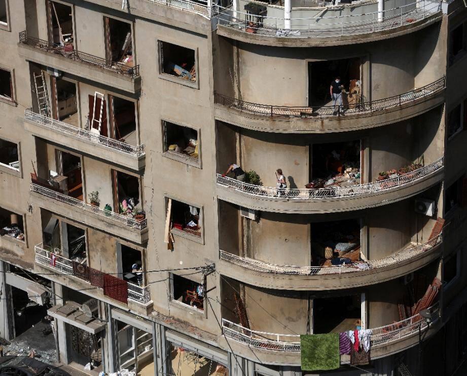 Des Libanais nettoient les débris dans leur immeuble à Beyrouth, soufflé par une violente explosion, le 6 août