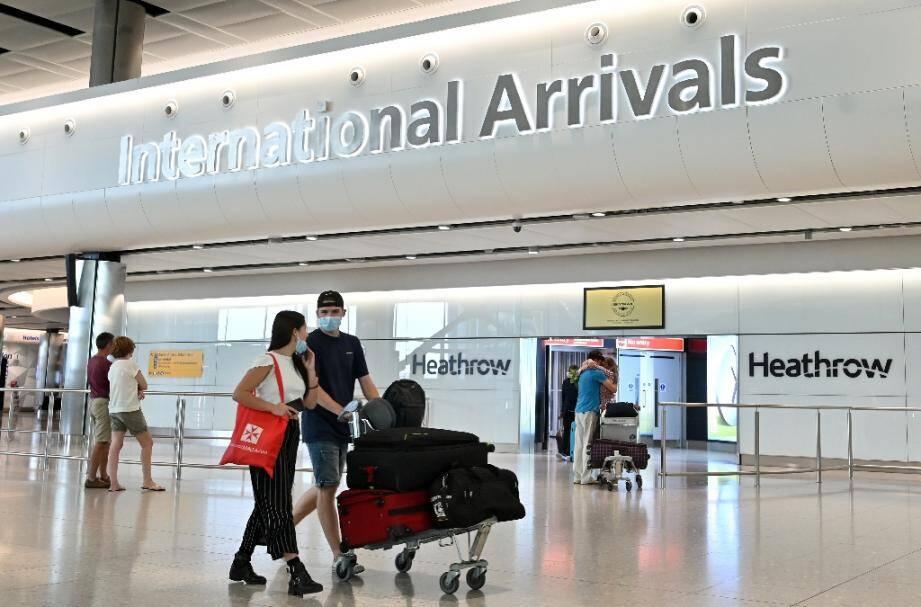 Des passagers portant un masque de protection contre le coronavirus arrivent à l'aéroport de Londres-Heathrow, le 9 mai 2020.