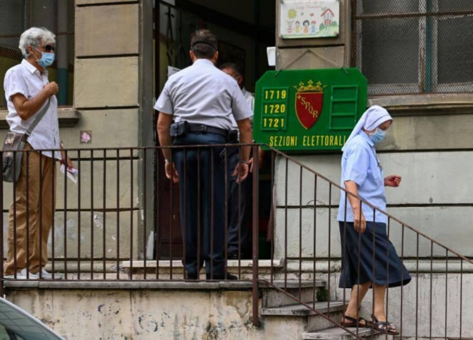 Une nonne portant un masque (à droite) quitte un bureau de vote après avoir voté, à Rome le 20 septembre 2020.