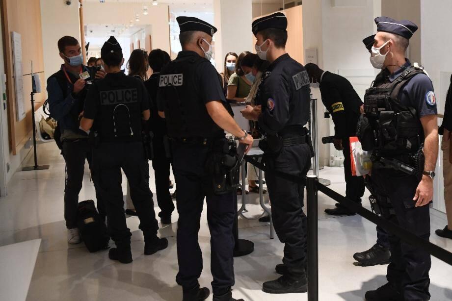 Des policiers contrôlent les personnes qui assistent au procès des attentas de janvier 2015 au tribunal à Paris, le 2 septembre 2020