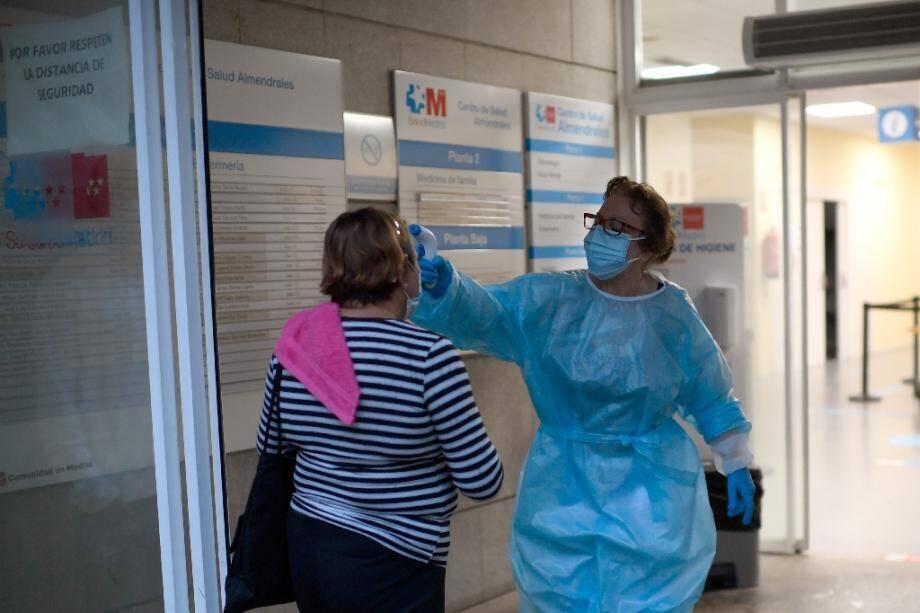 Une travailleuse médicale vérifie la température d'une visiteuse à l'entrée d'un centre de santé dans le quartier d'Usera, à Madrid, le 18 septembre 2020.