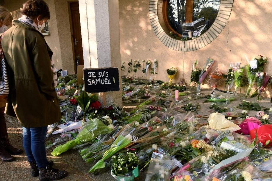 Adultes et enfants viennent déposer des fleurs devant le collège de Conflans-Sainte-Honorine, le 17 octobre 2020 au lendemain de la décapitation d'un des professeurs