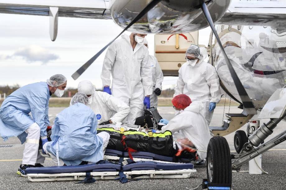Des équipes médicales évacuent un patient atteint du Covid-19 vers un hôpital où des lits de réanimation sont disponibles, le 27 octobre 2020 à l'aéroport de Bron, près de Lyon