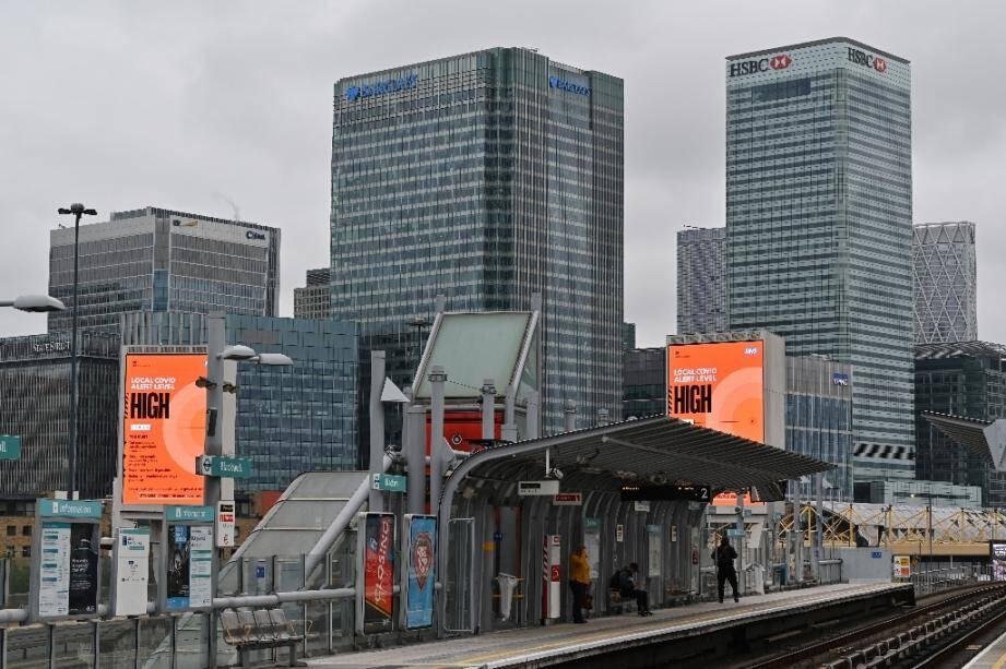 """Des passages attendent un métro tandis que des écrans signalent un niveau d'alerte """"élevé"""" au coronavirus, à Londres le 17 octobre 2020"""