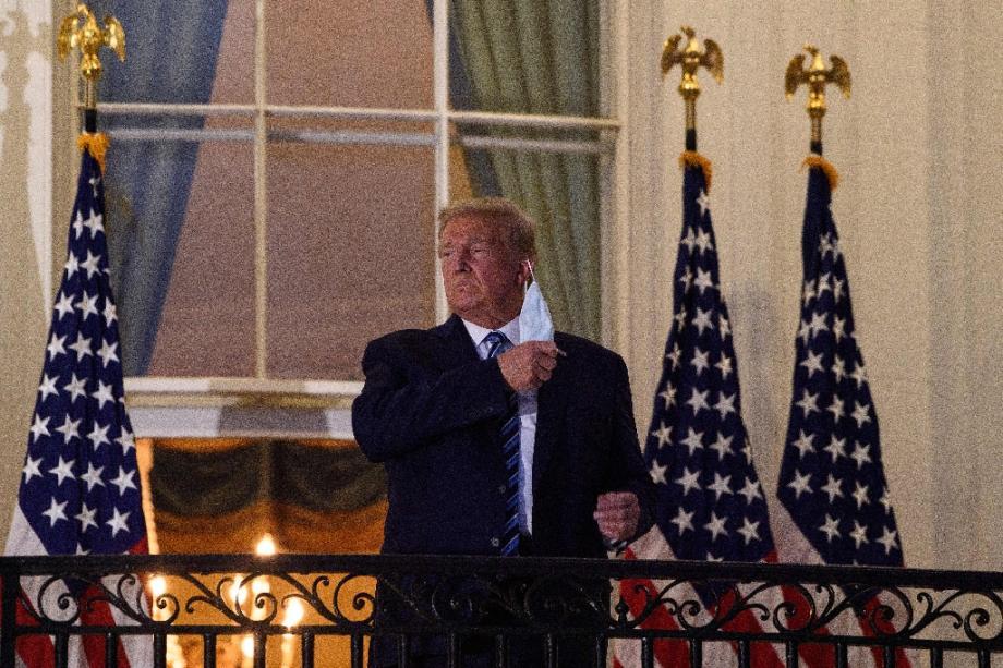 Le président américain Donald Trump retire son masque sur le balcon de la Maison Blanche après son retour de l'hôpital, le 5 octobre 2020