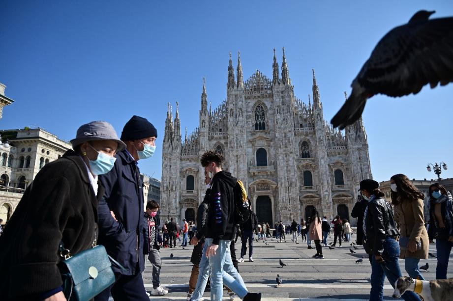 Des piétons portant des masques de protection passent devant le Duomo, la cathédrale de Milan (Italie), le 17 octobre 2020