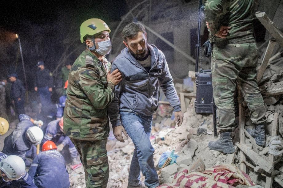 Un secouriste assiste un habitant sur un site touché par un missile à Gandja (Azerbaïdjan) le 17 octobre 2020