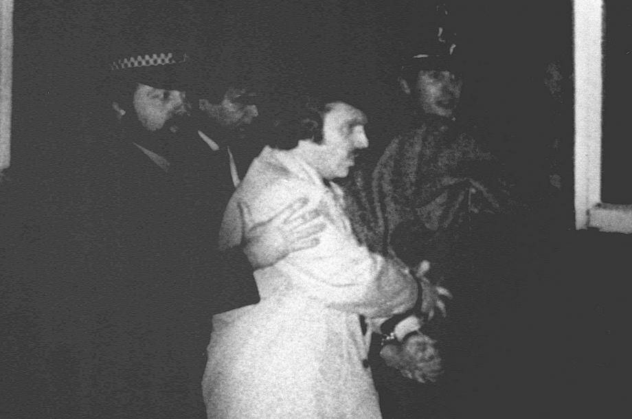 """Peter William Sutcliffe, suspecté d'être """"l'éventreur du Yorshire, est escorté le 06 janvier 1981 à Bradford par des policiers britanniques qui le conduisent à la cour de Dewsbury pour y être entendu et inculpé du 13ème crime commis par l'homme qui a """"fait trembler les villes situées près de Leeds, Bradford et Sheffield. Peter Sutcliffe, chauffeur de poids lourds de 35 ans, avait été arrêté le 02 janvier 1981 lors d'un simple contrôle de routine dans le """"quartier chaud"""" de Sheffield."""