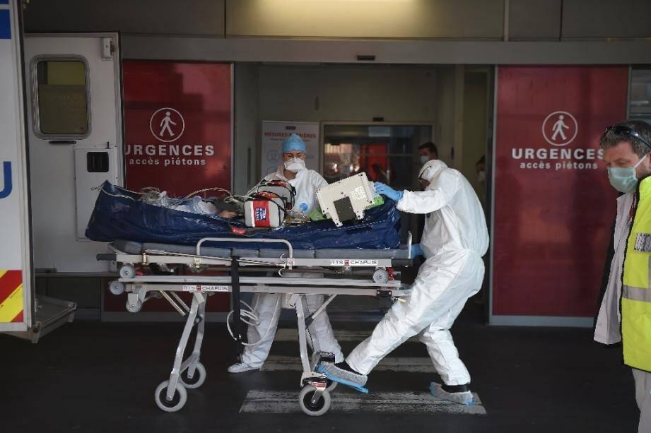 Du personnel médical transporte un patient infecté par le Covid-19 aux urgences de l'hôpital de Strabourg après son arrivée en avion depuis la région lyonnaise le 6 novembre 2020