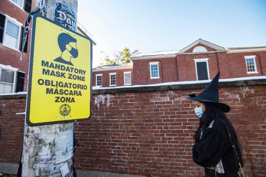 Une femme déguisée en sorcière pour Halloween devant un panneau qui signale l'obligation du port du masque, à Salem (Etats-Unis), le 31 octobre 2020