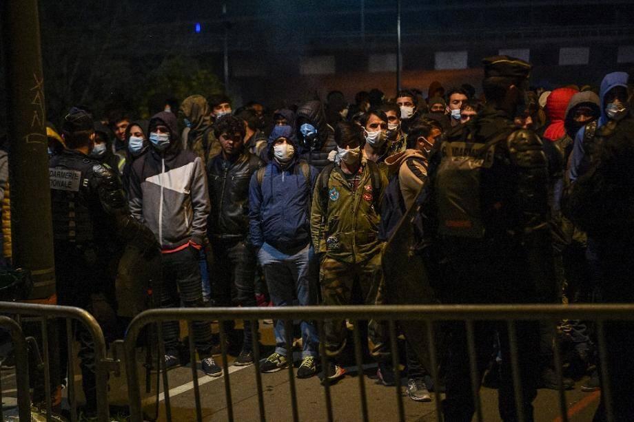 Des migrants attendent de monter dans les bus qui vont les acheminer vers des centres d'hébergement, le 17 novembre 2020 à Saint-Denis