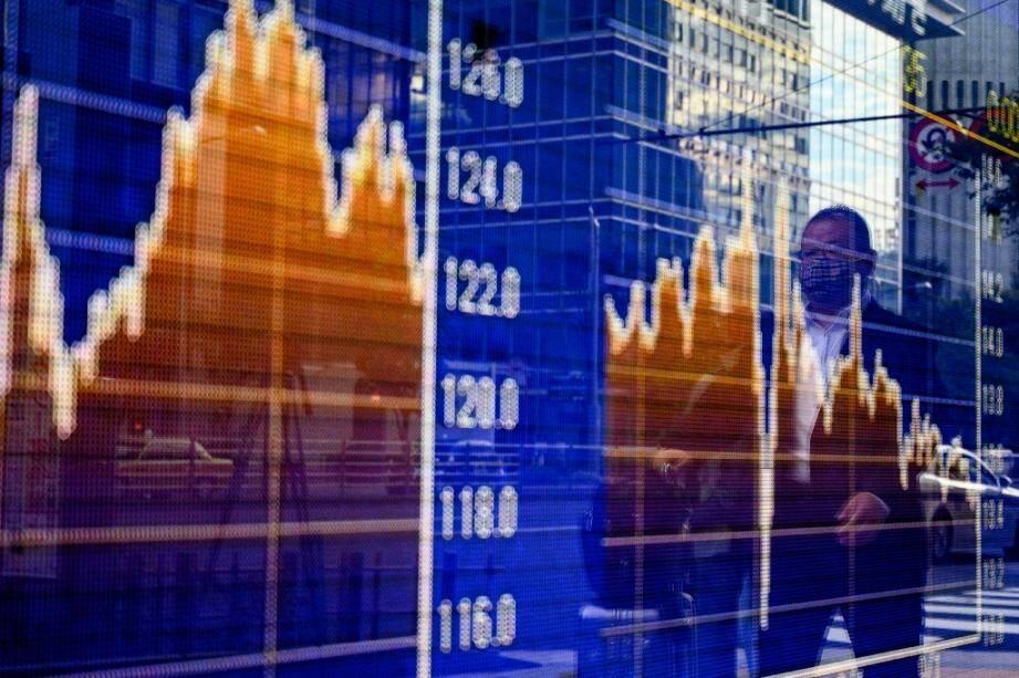 Des piétons passent devant les variations de la Bourse de Tokyo, le 6 novembre 2020
