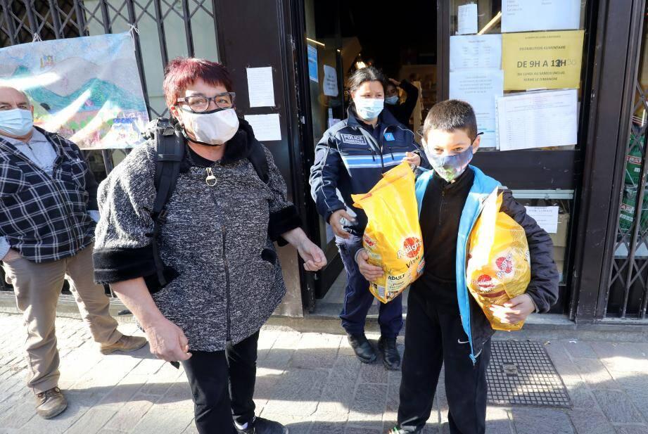 Marie-Jo Dalmasso et son petit-fils récupèrent de quoi nourrir leur famille et leur chien. Des dons salvateurs, en attendant la reprise incertaine d'une activité commerciale.