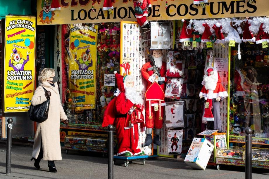 Une passante devant une boutique vendant des costumes de père Noël, à Paris, le 10 décembre 2020