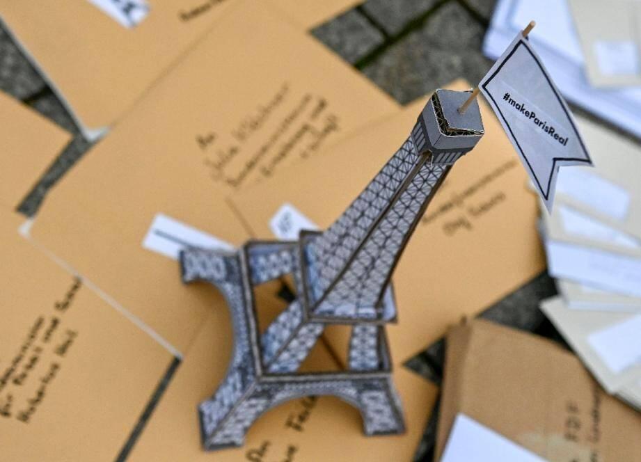 """Une tour Eiffel en carton couronnée d'un drapeau: """"Fais en sorte que Paris devienne une réalité"""" faite partie d'une installation posée par des activistes face à la porte de Brandenburg à Berlin le 11 décembre pour marquer les 5 ans de l'Accord de Paris sur le climat"""