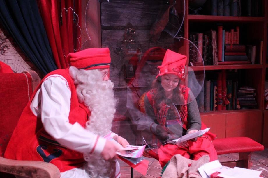 """Le Père Noël et son elfe Vanille, derrière un écran de plexiglas destiné à les protéger du coronavirus, le 17 décembre 2020 à Rovaniemi, en Laponie finlandaise, au parc d'attractions du """"Village du Père Noël"""""""