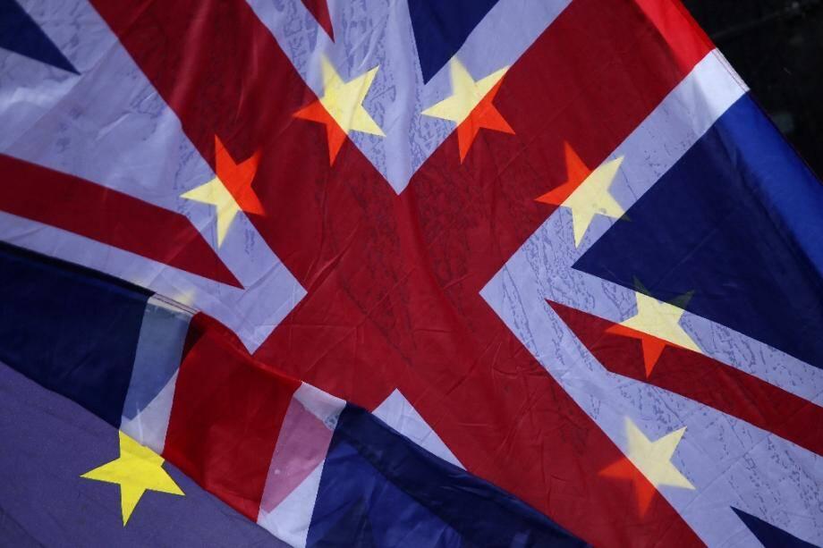 Des manifestants brandissent un drapeau européen derrière le drapeau britannique le 29 mars 2018 devant le parlement britannique à Londres