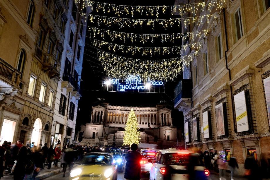 Rue commerçante Via del Corso, avec en arrière-plan l'arbre de Noël sur la Piazza Venezia, à Rome, le 13 décembre 2020