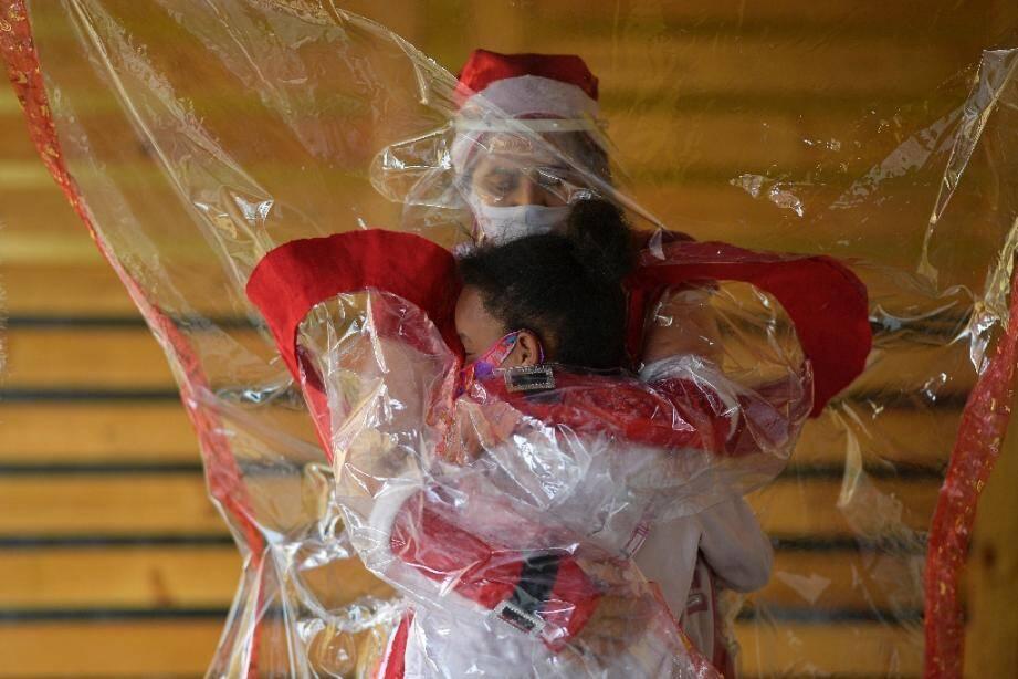Calin par temps de Covid-19 entre une bénévole et un enfant de Belo Horizonte dans l'Etat du Minas Gerais au Brésil, le 7 décembre 2020