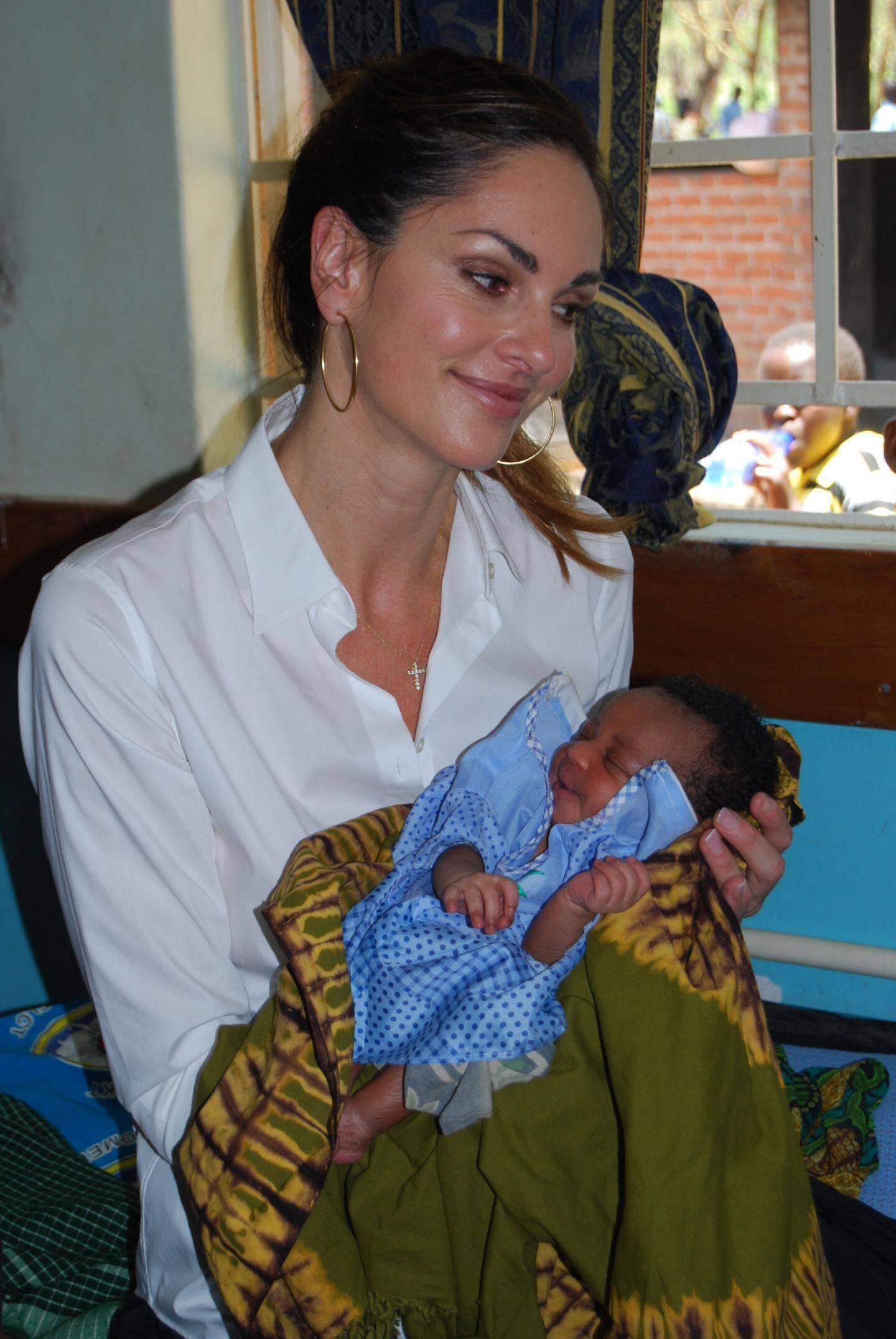 Tasha de Vasconcelos portant dans les bras un enfant né dans des conditions saines, dans un hôpital construit sous l'impulsion de sa fondation, AMOR, au Malawi.(DR)